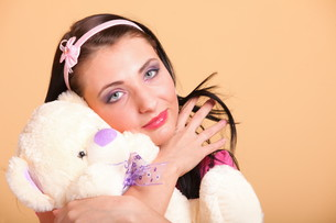 woman with pigtails hugging teddy bear toyの写真素材 [FYI00765804]