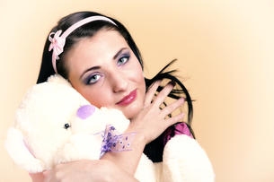 woman with pigtails hugging teddy bear toyの写真素材 [FYI00765809]