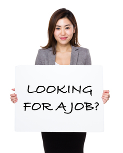 Confident businesswoman showing a poster showing with looking for a job phrasesの写真素材 [FYI00766001]