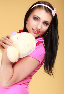 childish young woman in pink infantile girl hugging teddy bear toyの素材 [FYI00767295]