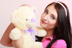 childish young woman in pink infantile girl hugging teddy bear toyの写真素材 [FYI00767296]