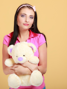 childish young woman infantile girl in pink hugging teddy bear toyの写真素材 [FYI00767297]
