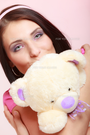infantile childish young woman kissing a girl in pink teddy bear toyの写真素材 [FYI00767301]