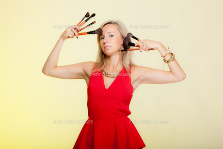 beauty procedures,woman holds make-up brushes near face.の写真素材 [FYI00767328]