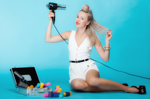 sexy girl retro styles in curlers with a hairdryer styling hairの写真素材 [FYI00767338]