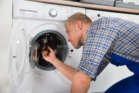 Repairman Repairing Washerの写真素材 [FYI00767578]