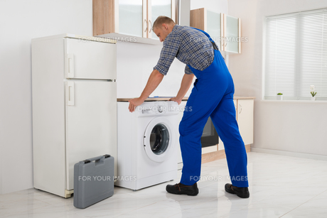 Worker Repairing Washerの写真素材 [FYI00767582]