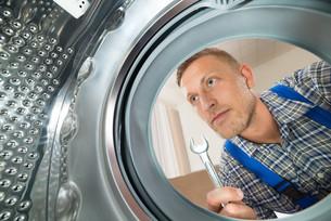 Repairman Looking Inside The Washing Machineの写真素材 [FYI00767583]