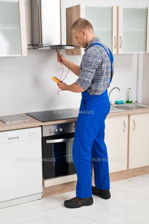 Worker Testing Kitchen Hood With Multimeterの写真素材 [FYI00767600]