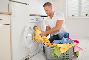 Man Putting Dirty Clothes Into The Washing Machineの写真素材 [FYI00767613]