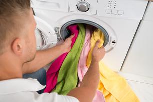 Man Loading Towels Into The Washing Machineの写真素材 [FYI00767615]