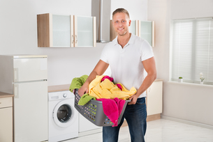 Man Carrying Laundry Basket In Kitchen Roomの写真素材 [FYI00767616]