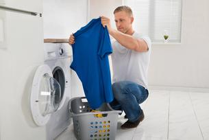 Man With T-shirt While Using Washing Machineの写真素材 [FYI00767621]