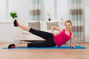 Woman In Sportswear Exercising At Homeの写真素材 [FYI00767625]