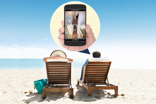 Couple relaxing on deck chairs at beach resortの写真素材 [FYI00767640]