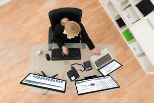 Businesswoman Analyzing Financial Statistics On Computerの写真素材 [FYI00767657]
