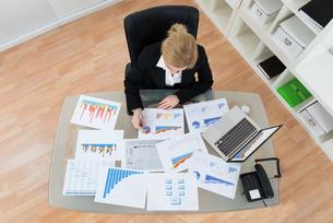 Businesswoman Analyzing Financial Graphsの写真素材 [FYI00767662]