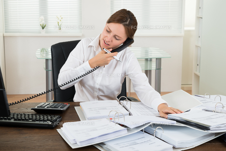 Businesswoman Using Telephone While Doing Accountingの写真素材 [FYI00767688]