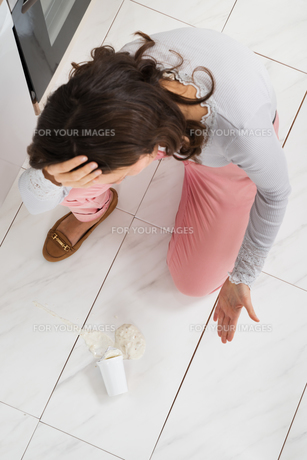 Woman Looking At Yoghurt Spilled On The Floorの写真素材 [FYI00767764]