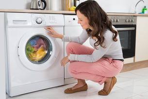 Woman Looking At Clothes Rotating Inside The Washing Machineの写真素材 [FYI00767770]