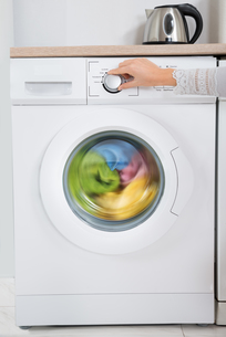 Person Hands Turning Button Of Washing Machineの写真素材 [FYI00767773]