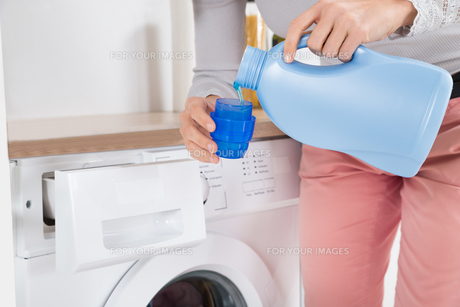 Female Hands Pouring Detergent In The Bottle Capの写真素材 [FYI00767776]