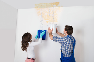 Woman And Repairman Collecting Water From Ceilingの写真素材 [FYI00767800]