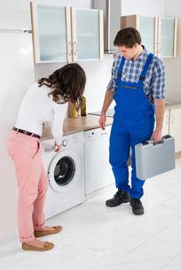 Woman Showing Damage In Washing Machine To Repairmanの写真素材 [FYI00767801]
