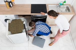 Woman Looking At The Repairman Repairing Dishwasherの写真素材 [FYI00767802]