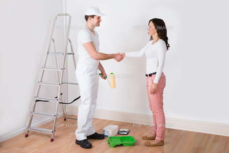 Woman Shaking Hands To Painter With Paint Roller At Homeの写真素材 [FYI00767803]