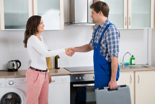 Repairman Shaking Hands With Womanの写真素材 [FYI00767812]