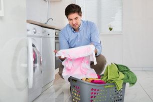 Man With Laundry Basket Holding Stained Clothの写真素材 [FYI00767816]