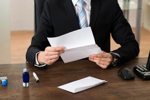 Businessman Holding Document At Deskの写真素材 [FYI00767843]