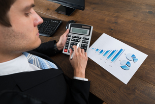Businessman Analyzing Financial Data With Calculatorの写真素材 [FYI00767861]