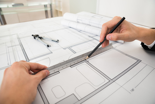 Engineer Drawing Diagrams On Blueprint Paperの写真素材 [FYI00767867]