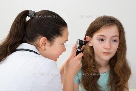 Doctor Examining Patient Ear With Otoscopeの素材 [FYI00767871]