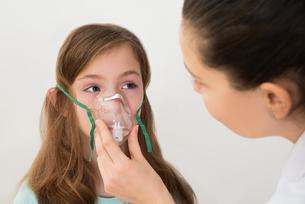 Doctor Holding Inhaler Mask For Girl Breathingの写真素材 [FYI00767878]