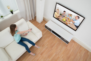 Girl Holding Remote Control In Front Of Televisionの写真素材 [FYI00767886]