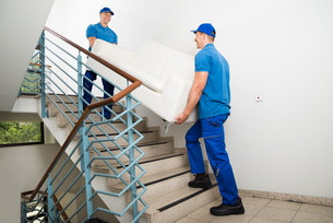 Two Male Movers Carrying Sofa On Staircaseの写真素材 [FYI00768142]