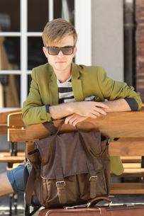 young handsome man with bag waits on benchの素材 [FYI00768381]