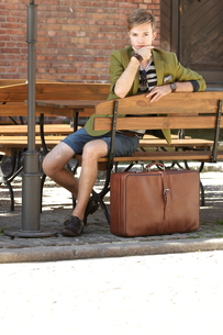 young handsome man with suitcase waits on benchの素材 [FYI00768388]