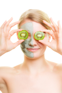 skin care. woman in clay mask with kiwi on faceの写真素材 [FYI00768507]