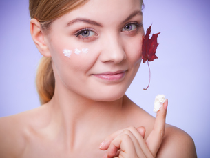 skin care. face of young woman girl with red maple leaf.の写真素材 [FYI00768528]