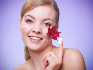 skin care. face of young woman girl with red maple leaf.の写真素材 [FYI00768535]