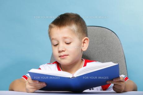 child boy kid reading a book on blueの素材 [FYI00768538]