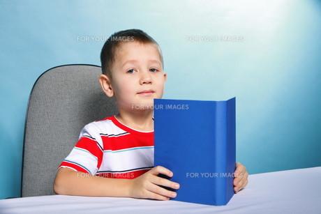 child boy kid reading a book on blueの素材 [FYI00768539]
