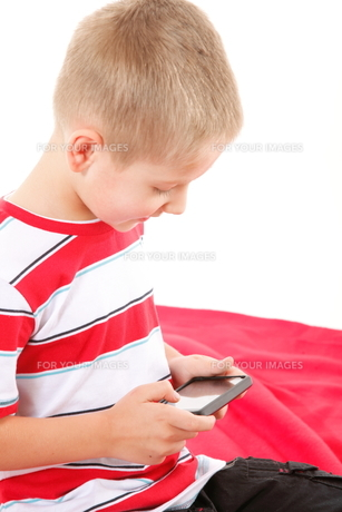 child plays games on the mobile phoneの写真素材 [FYI00768600]