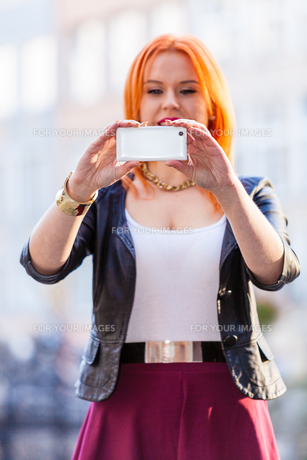 woman taking self picture with a smartphone cameraの写真素材 [FYI00768626]