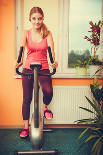 woman on exercise bike listening music. fitnessの写真素材 [FYI00768802]