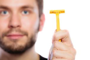 young man with beard showing razor bladeの素材 [FYI00768830]